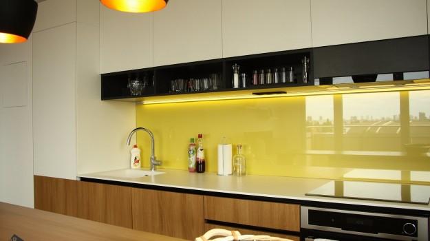 interier-bytu-novostavba-kadnarova-ul-bratislava-040-navrh-architekt-jednoducha-kuchyna-nadcasova-biela-pracovna-doska-himacs-detail-kuchynskej-linky-dvierka-orech-zlta-zastena-lakobel-police-na-pohare