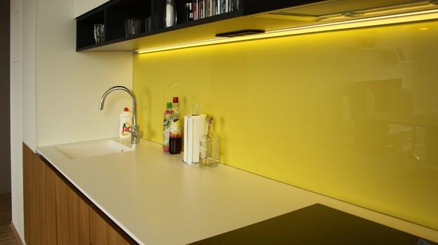 interier-bytu-novostavba-kadnarova-ul-bratislava-046-navrh-architekt-jednoducha-kuchyna-nadcasova-biela-pracovna-doska-himacs-detail-kuchynskej-linky-dvierka-orech-zlta-zastena-lakobel-police-na-pohare