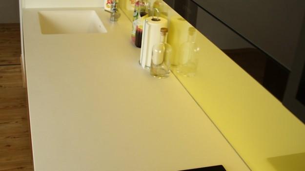 interier-bytu-novostavba-kadnarova-ul-bratislava-047-navrh-architekt-jednoducha-kuchyna-nadcasova-biela-pracovna-doska-himacs-detail-kuchynskej-linky-dvierka-orech-zlta-zastena-lakobel