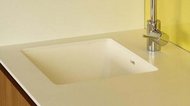 interier-bytu-novostavba-kadnarova-ul-bratislava-084-navrh-interierovy-architekt-moderna-biela-kuchyna-pracovna-doska-himacs-andromeda-drez-z-himacsu-pure-white-detail-drezu-dvierka-orech-zlta-zastena-lakobel